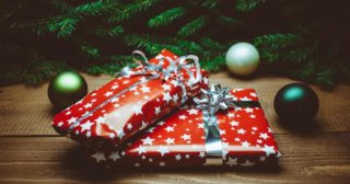 Two Christmas presents wrapped in red wrapping paper with baubles scattered around them