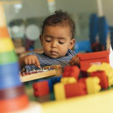 Toddler plays with multicoloured bricks in childcare setting