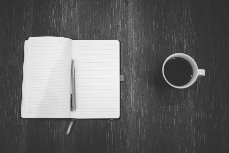 Blank notebook open on grey table with pen lying on the pages and a coffee cup beside the book