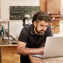 Bearded man in black t shirt working at laptop in his kitchen