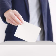 Voting. Man putting a ballot into a voting box.