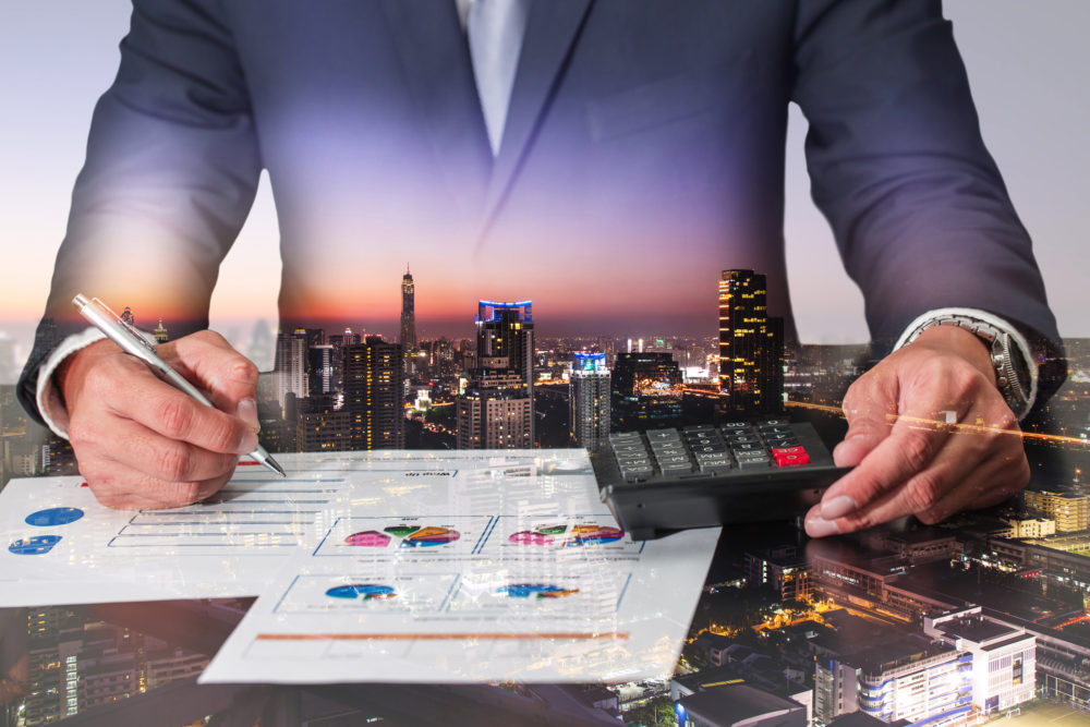 double exposure of businessman working with document and calculator for analyze in the work, cityscape, urban and street in the night as analysis and commitment concept.