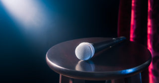 A microphone on a wooden stool with red curtain in the background
