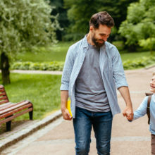 Dad walking in park with son who is carrying school bag