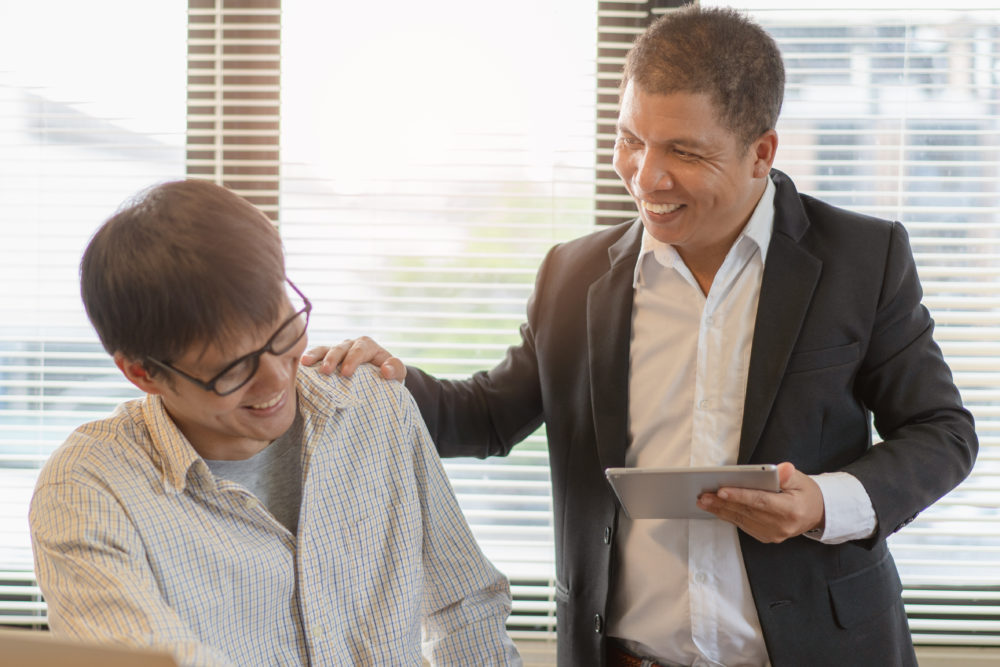 Man in white shirt and suit puts encouraging hand on shoulder of employee wearing a shirt