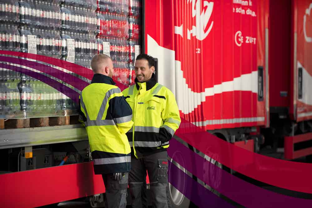 Two men chatting next to a coca cola truck