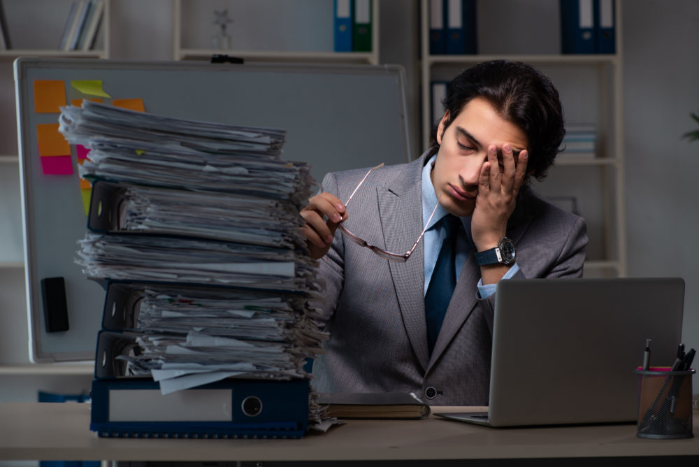 Young male in suit and holding his head in his hands in front of a computer and a huge stack of papers