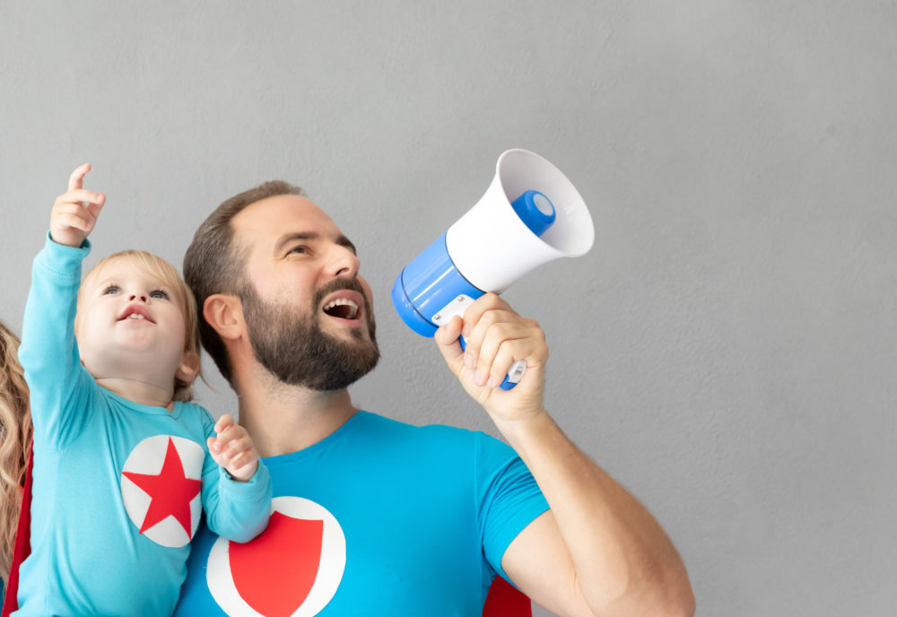 Man and woman in superhero costumes shouting through loudhailer and holding baby