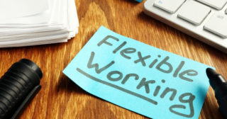 The words flexible working written on a post it note next to a keyboard and a pen