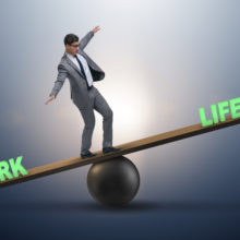 Businessman on plank balanced on a ball with the word Work at one end and the word Life at the other