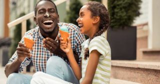 Dad and daughter laugh and eat ice cream