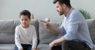 Child and man on grey couch, man is pointing finger to discipline child