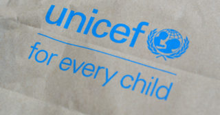 Blue unicef logo on a paper bag