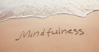 mindfulness written in sand on the beach