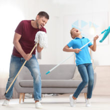 Dad and son having fun pretending to play guitar on mops while cleaning living room together