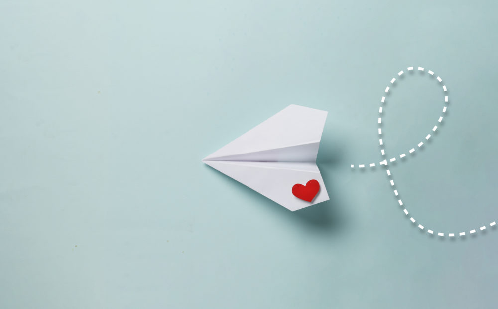 paper love airplane on color background Valentine's Day