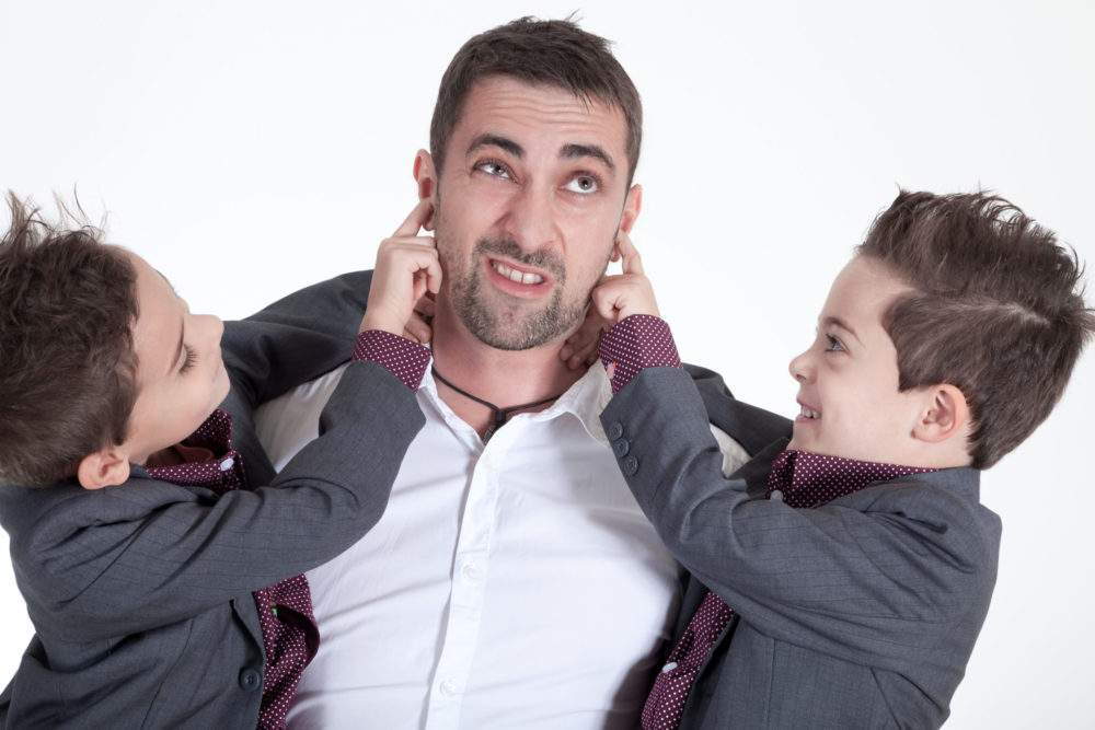 Man holding two children, each putting a finger in his ear
