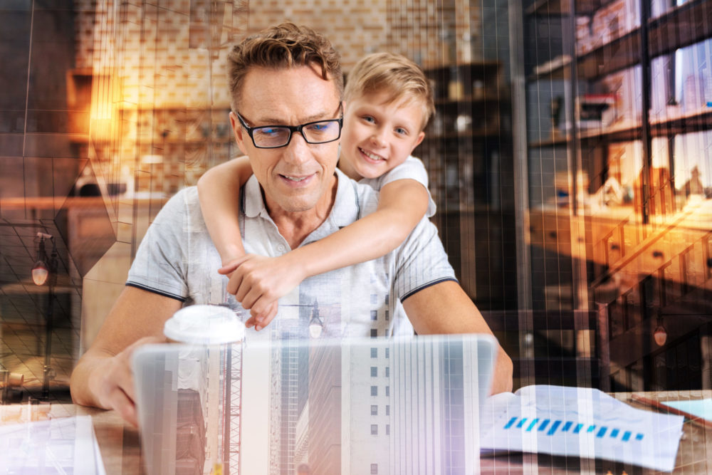 Working dad. Smart attentive man in glasses sitting in front of a laptop and looking at the screen of it while his friendly cheerful son standing behind his back with arms on shoulders of a father