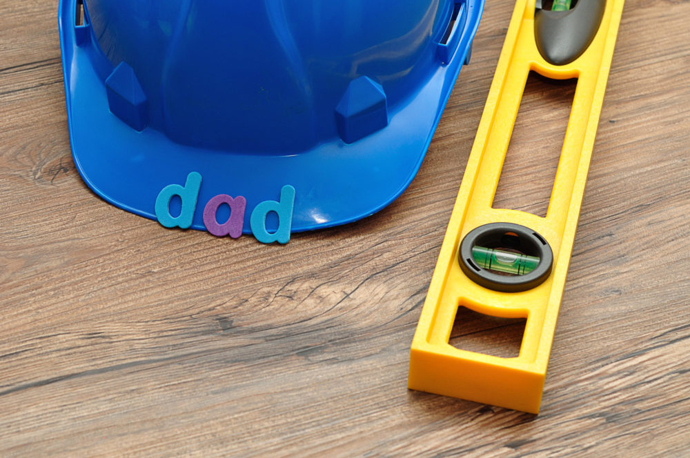 The word dad displayed with a level and a blue hardhat