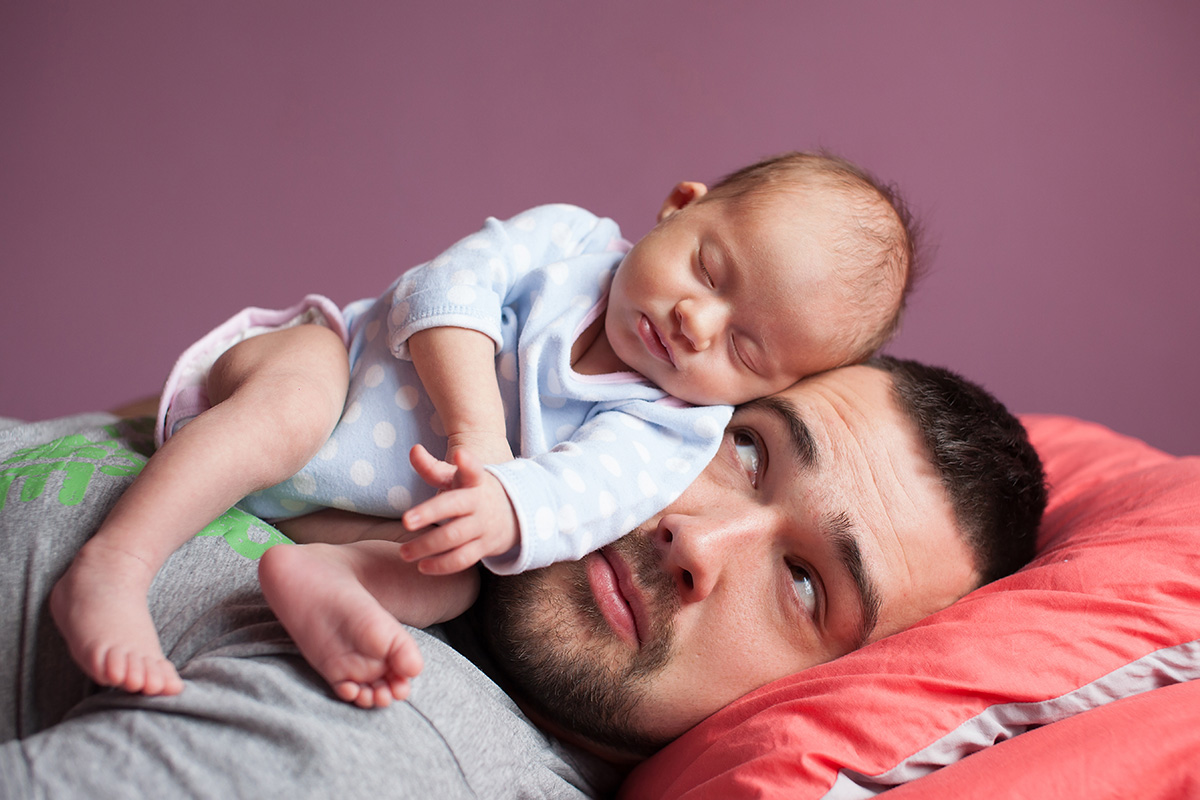 Baby lying on father
