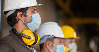 Construction workers in hard hats and face masks