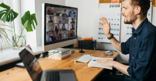 man sitting at home office desk on a zoom call