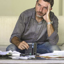 Man looking stressed surrounded by receipts and calculator
