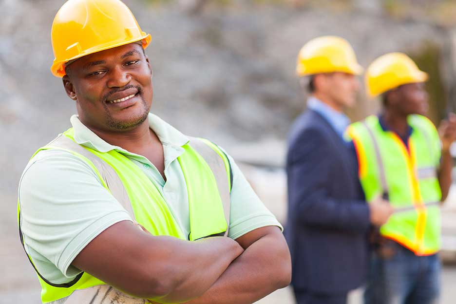 Construction worker smiles to camera
