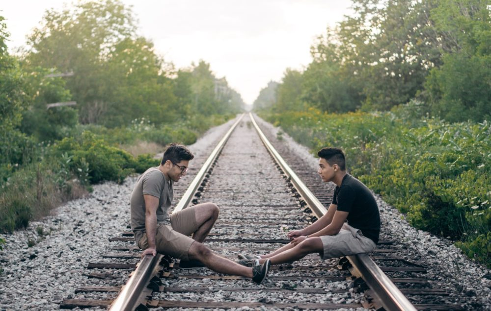Two men having a conversation on a railway line