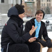 Two men sitting on a bench in a snowy city talking having a conversation