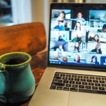 Laptop open with many screens on it as in a zoom meeting with coffee cup to the side