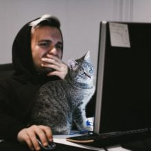 Man in black hoodie sat at computer with cat on the keyboard