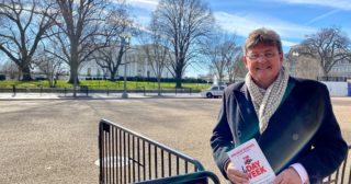 Author Andrew Barnes outside the White House with his book on the four day week