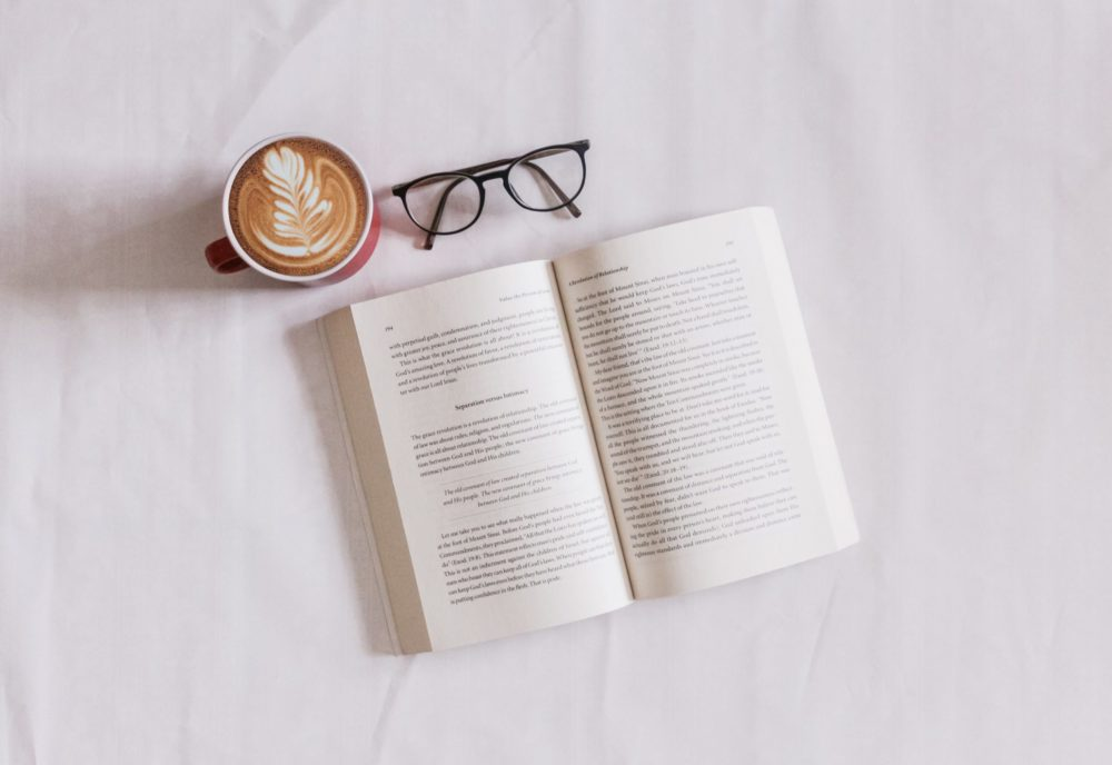 Open book, pair of glasses and coffee cup on a white background