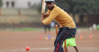 Man lifting cricket bat to hit pink ball
