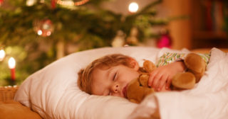 Little blond boy asleep next to Christmas tree and hugging a teddy bear