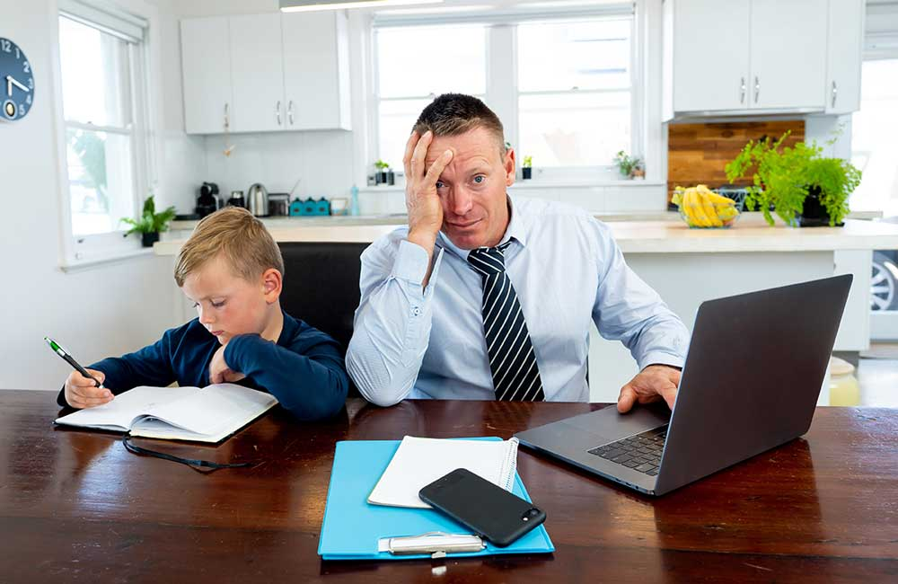 Stressed looking dad works at kitchen table whilst looking after small boy