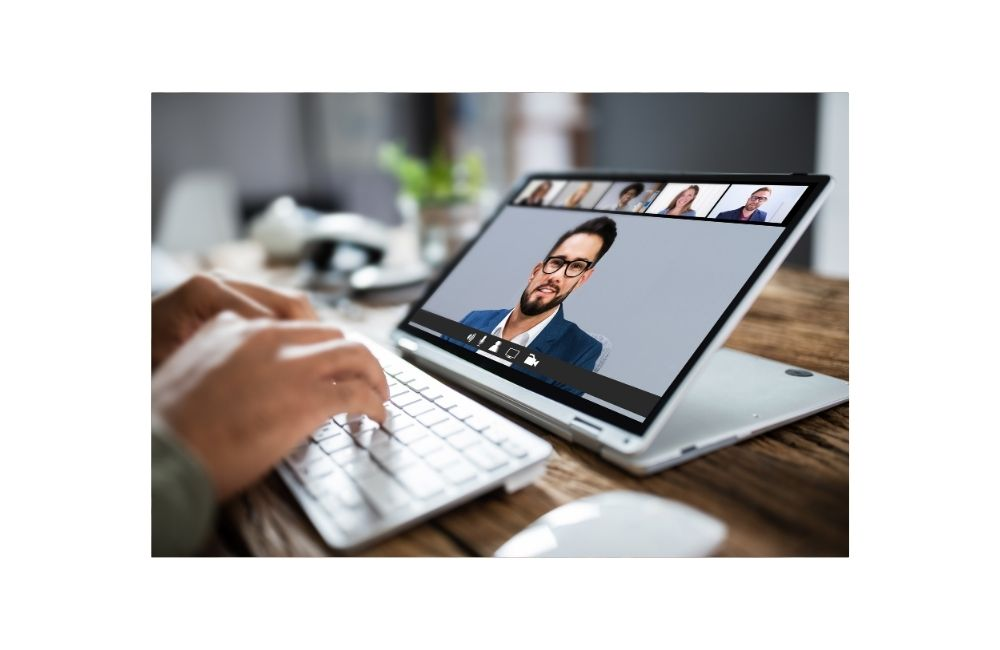 Open laptop featuring man's face in Zoom meeting and hands typing on the keyboard of the laptop
