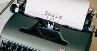 vintage typewriter containing sheet of paper on which is written GOALS
