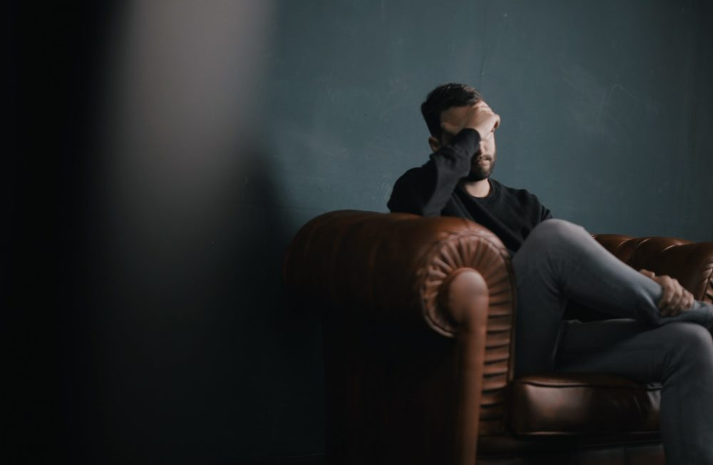 Man sitting on couch with head in hands looking stressed