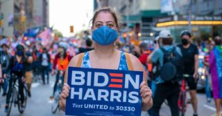 Woman in New York street wearing face mask and holding Biden Harris placard in support of Joe Biden