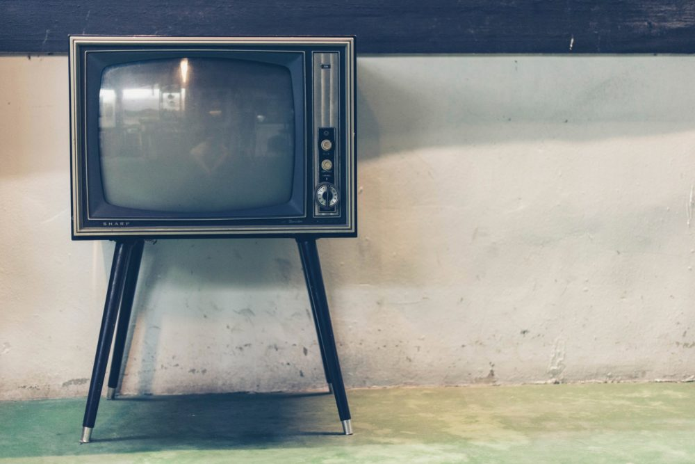 old fashioned television on a four legs against a plain wall