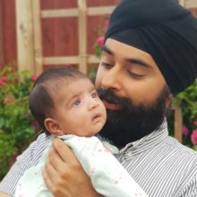 Harpreet Likhari in grey shirt and black turban holding baby Mehr with rose bushes in the background