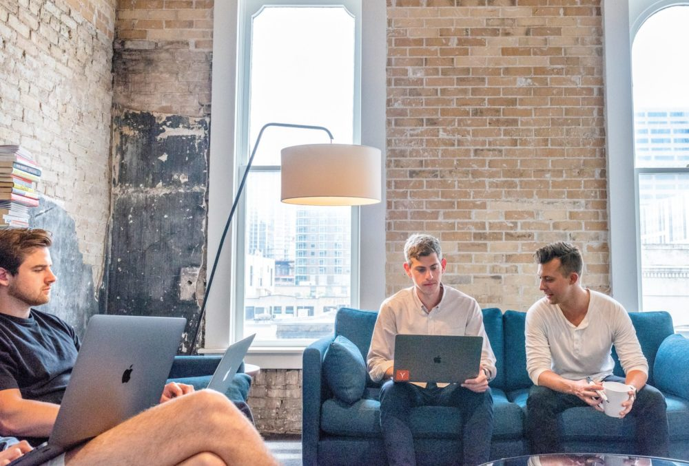 three men sitting on sofas with laptops doing flexible working