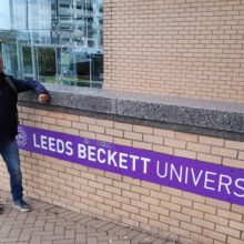 Transition to Teach man Dean Fletcher standing by wall with Leeds Beckett University sign