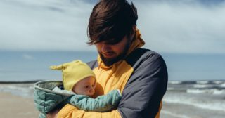 anxious dad cradles baby on a windy beach